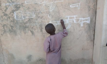 Sad situation of life in the Northern Nigeria as it can be seen from a photo of a little boy drawing guns